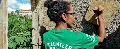 A Projects Abroad volunteer helps with plastering a wall during her volunteer building work abroad.